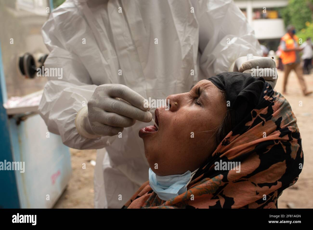 Dhaka, Bangladesh. 10 Apr 2021. Una donna reagisce come un operatore sanitario che indossa dispositivi di protezione individuale prende un bastoncino da lei per testare la malattia di coronavirus (COVID-19) in un ospedale di Dhaka. Credit: Fatima-Tuj Johora/ZUMA Wire/Alamy Live News Foto Stock