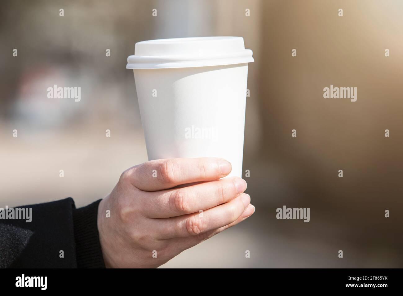 Tazza di carta con caffè in mano della donna. La mattina presto, la colazione e l'inizio del lavoro da. Spazio vuoto per testo, mockup. Foto Stock