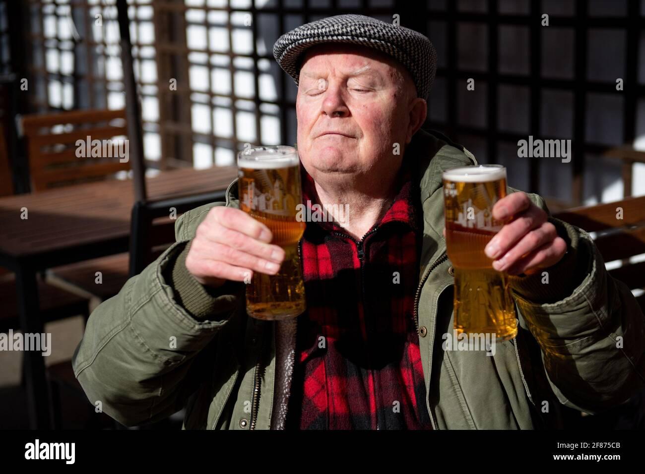 John Witts gode di un drink alla riapertura del pub The Figure of Eight, a Birmingham, mentre l'Inghilterra fa un altro passo indietro verso la normalità con l'ulteriore allentamento delle restrizioni di blocco. Data immagine: Lunedì 12 aprile 2021. Foto Stock