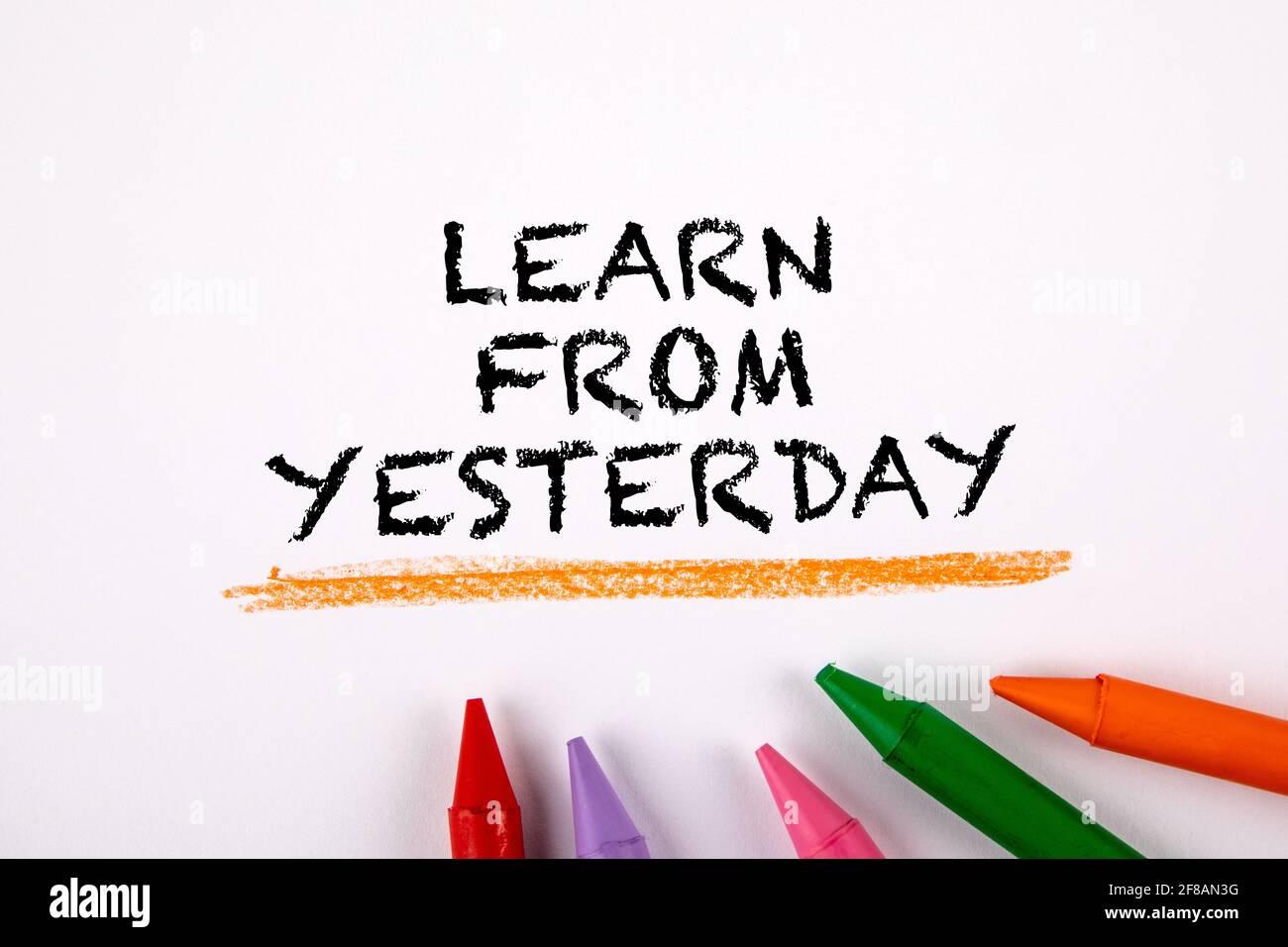 Impara da ieri. Pastelli colorati su sfondo bianco. Foto Stock