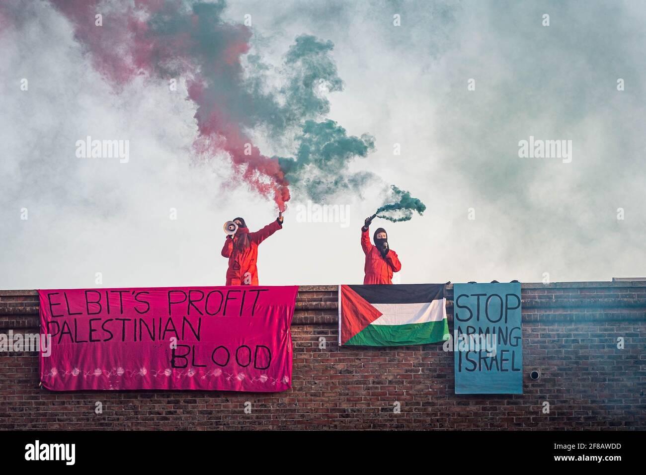 """Bristol, Regno Unito. 13 Apr 2021. Gli attivisti Palestine Action occupano il tetto del quartier generale di Elbit a Bristol nelle prime ore di mercoledì mattina. Le bandiere appendono dal tetto leggere """"il profitto di Elbit sangue palestinese"""" e """"smettere di armare Israele"""". Aztec West Business Park a Bristol, Regno Unito. Credit: Vladimir Morozov/akxmedia. Credit: Vladimir Morozov/Alamy Live News Foto Stock"""