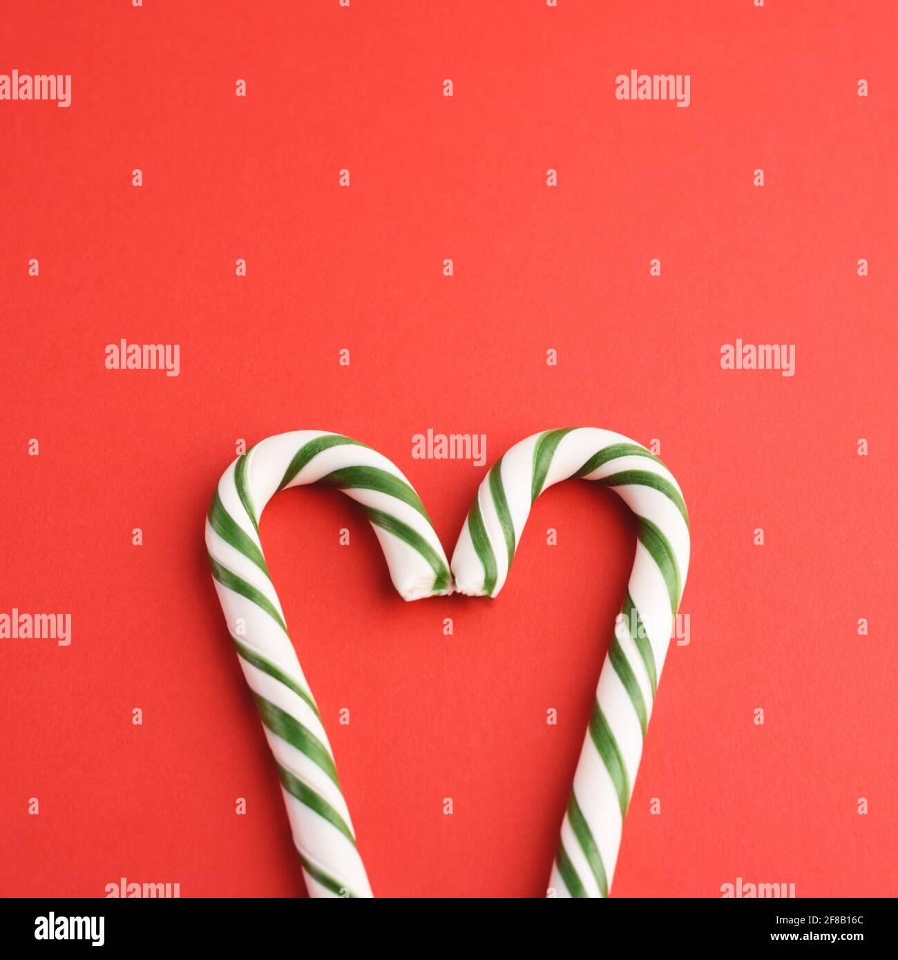 Caramelle dure a forma di cuore bianco e verde a strisce natalizie sul dorso rosso. Foto Stock