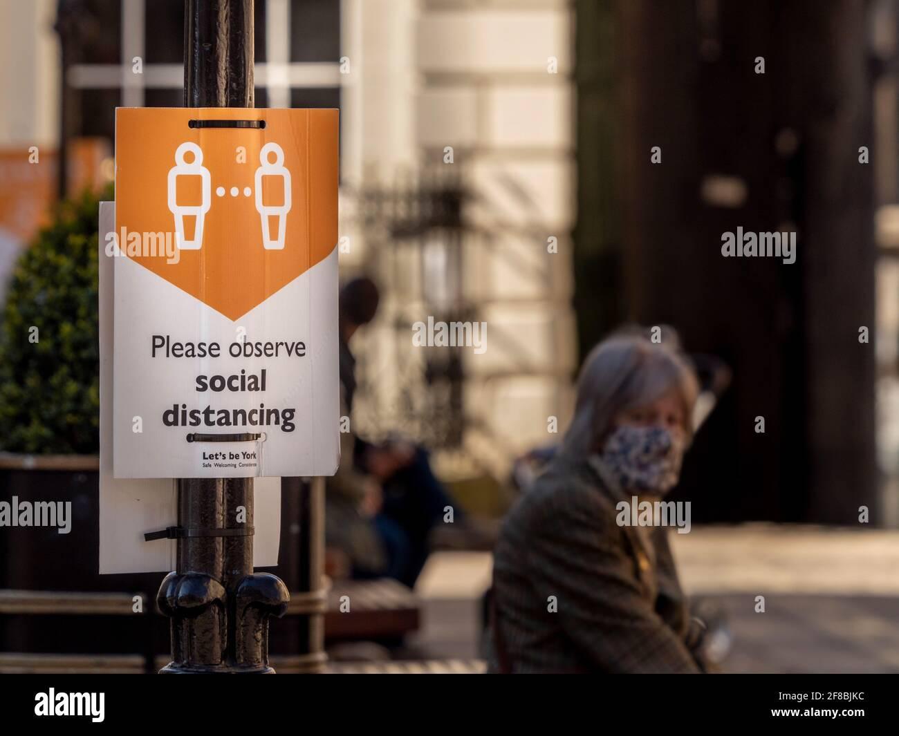 Caucasico caucasico indossare un volto di copertura seduta da un segno sociale di distanza a York, dopo aver alleggerito le restrizioni di blocco covid-19. Foto Stock