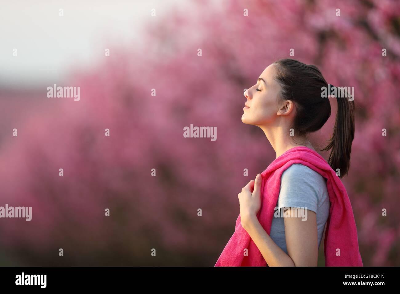 Profilo di una sportiva che respira aria fresca dopo lo sport in un campo fiorito rosa Foto Stock