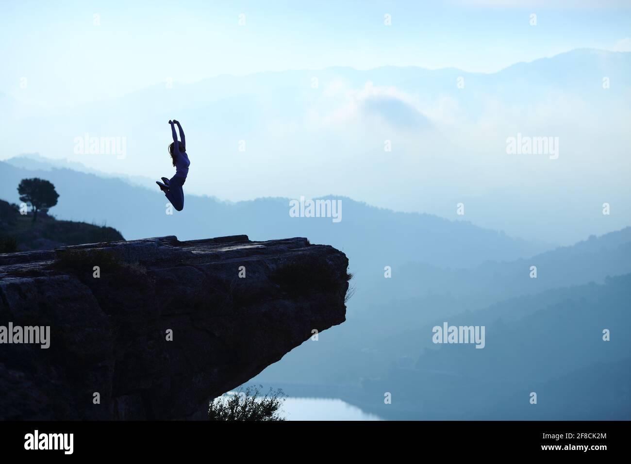Ritratto retroilluminato di una silhouette donna che salta in alto di una scogliera sul paesaggio blu Foto Stock