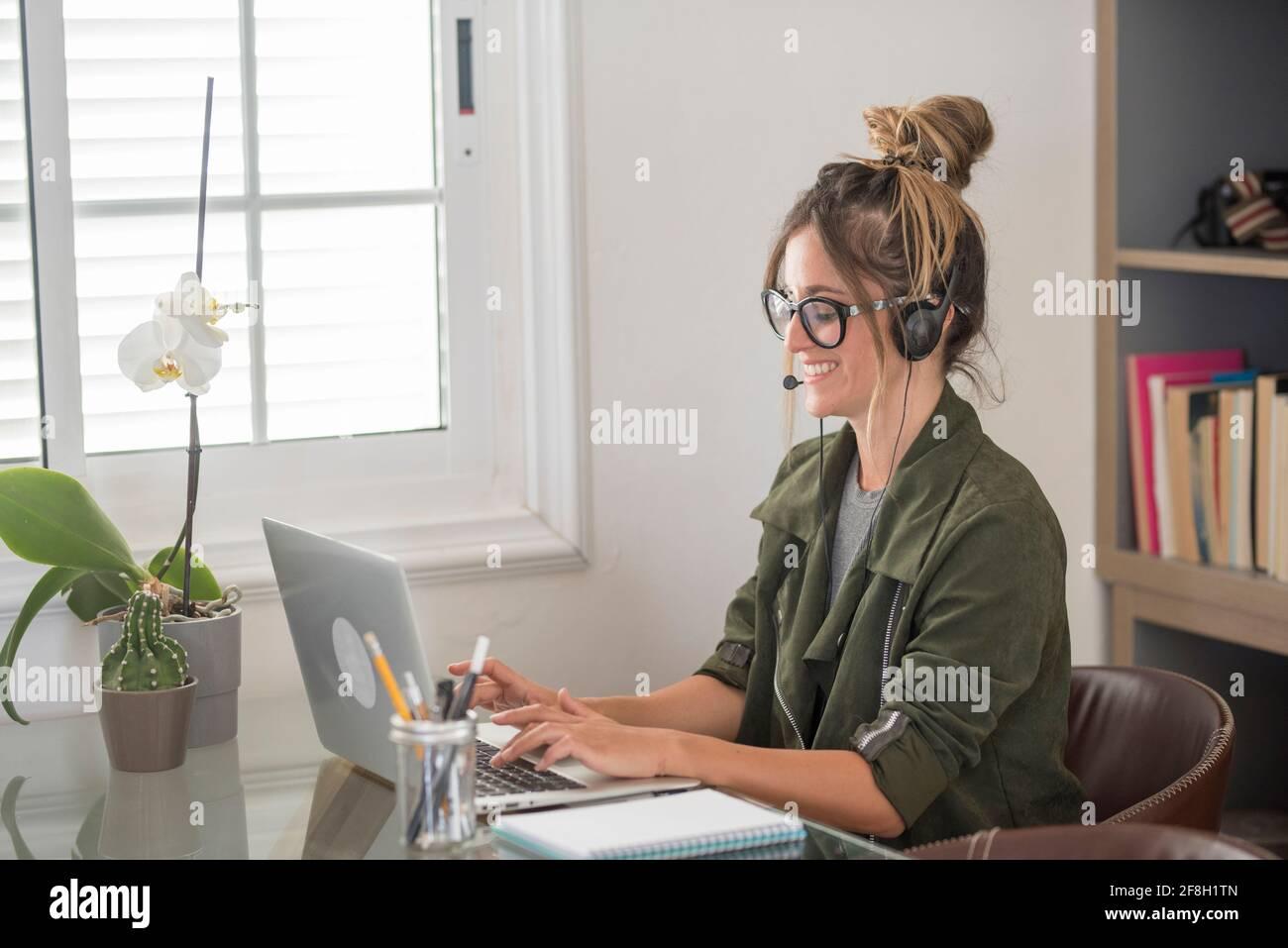 Felice giovane donna adulta in videochiamata conferenza a casa nello stile di vita di lavoro alternativo intelligente e libero dell'ufficio - grazioso le donne ricevono notizie su Foto Stock