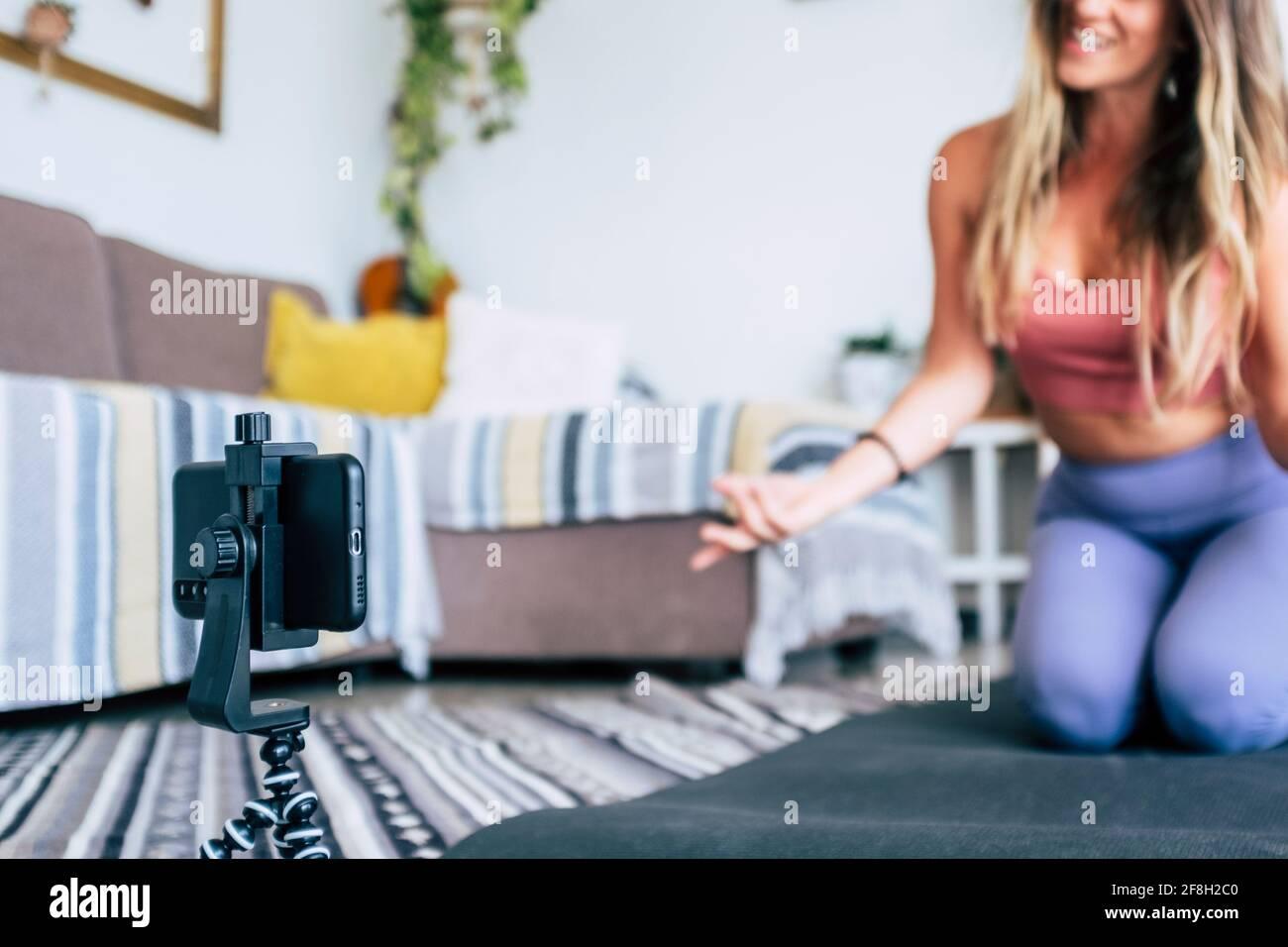Giovane donna che si esercita a casa facendo l'allenamento e la registrazione a. lei con il telefono cellulare per insegnare l'allenamento e produrre il web classe - attività di creazione di contenuti Foto Stock