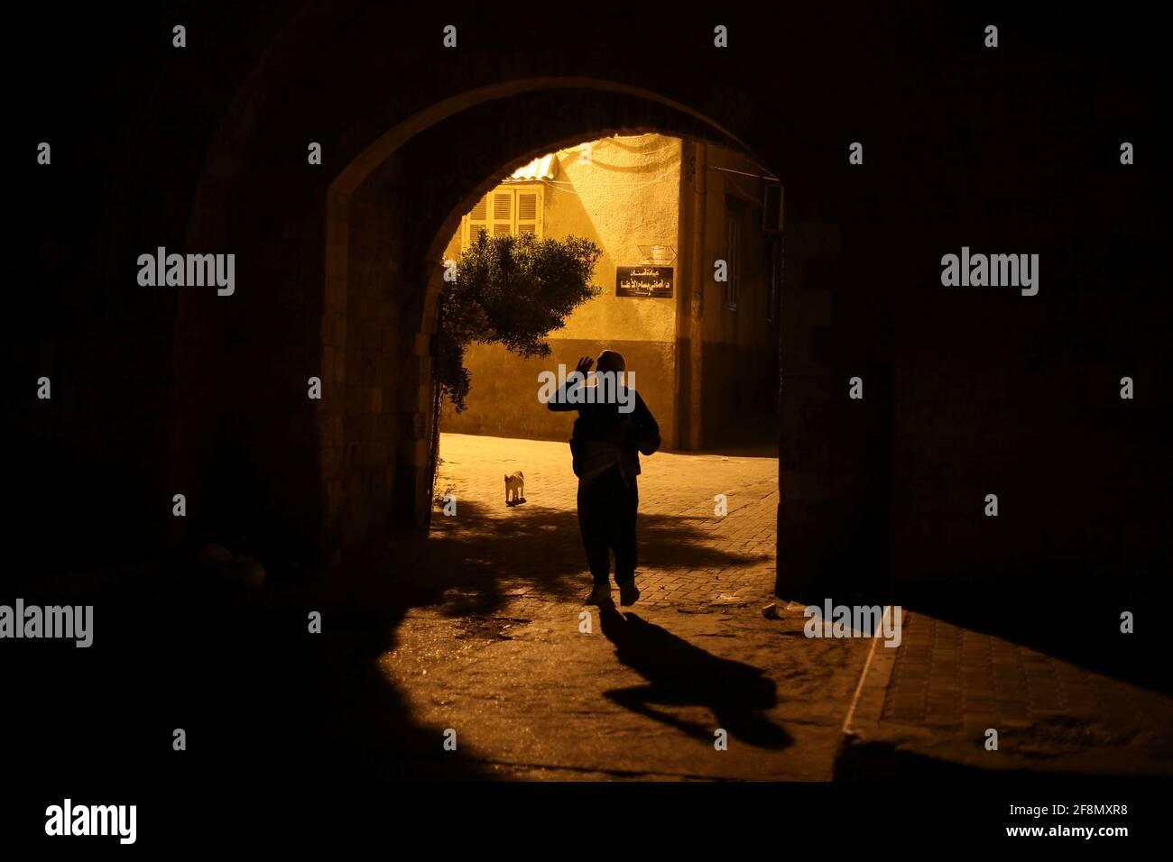 Un Mesaharati palestinese tiene un tamburo mentre chiede di svegliare i musulmani per avere il pasto prima dell'alba prima che comincino il loro digiuno di lunga giornata, durante il mese santo del Ramadan, in mezzo all'epidemia di coronavirus (COVID-19), a Khan Young nella striscia di Gaza meridionale 15 aprile 2021. REUTERS/Ibraheem Abu Mustafa Foto Stock