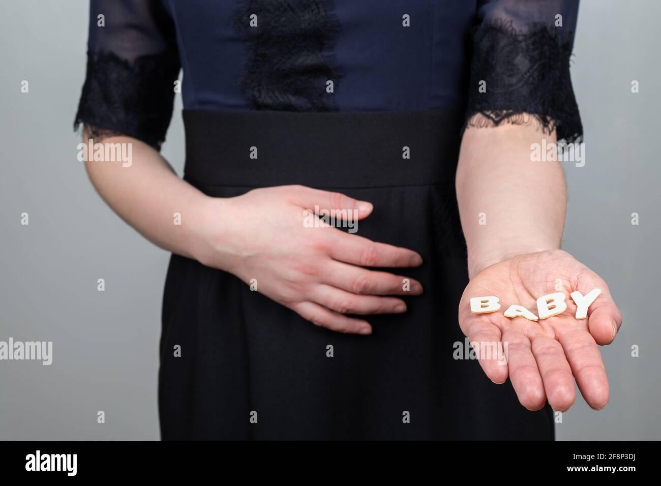 Donna incinta. Word Baby da lettere alfabetiche in legno. Foto Stock
