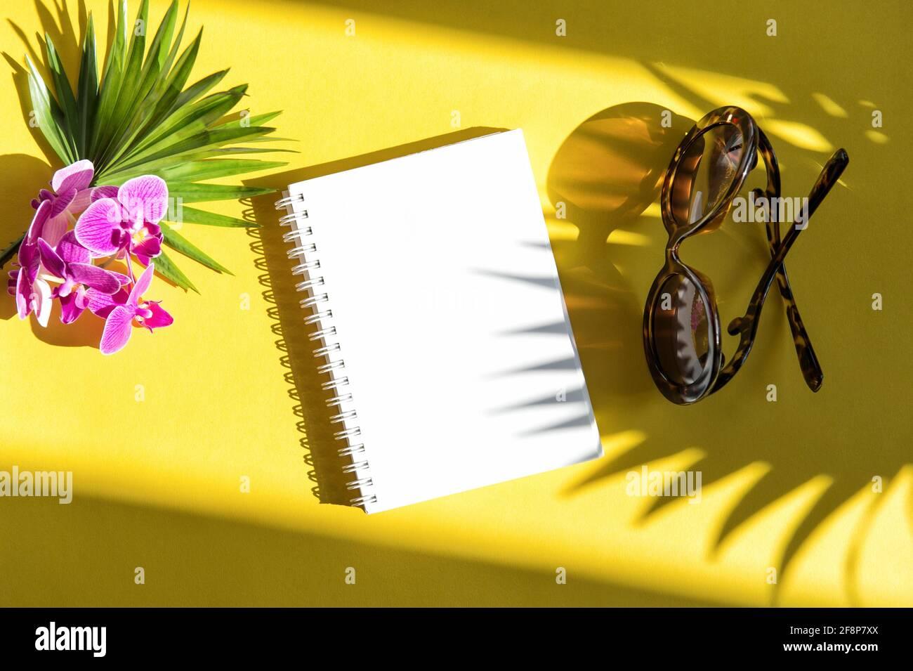 Appartamento estivo con ombra. Taccuino, occhiali da sole, foglia di palma, orchidea fiore su sfondo giallo Foto Stock