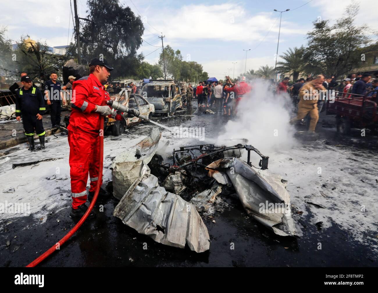 Un vigile del fuoco ispeziona il sito di un attentato all'automobile intrappolata nel distretto di Sadr City di Baghdad, Iraq, 15 aprile 2021. REUTERS/Wissam al-Okili Foto Stock