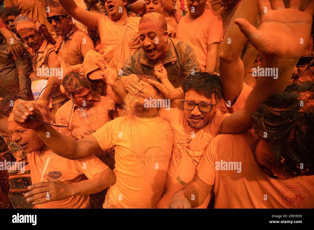 Bhaktapur, Nepal. 15 Aprile 2021. I devoti giocano con polvere di vermiglio mentre celebrano il festival della polvere di vermillion di Jatra. I rivelatori portarono carri degli dei e delle dea indù e si gettarono vermilioni di polvere l'uno sull'altro come parte delle celebrazioni che iniziarono il nuovo anno nepalese. Credit: SOPA Images Limited/Alamy Live News Foto Stock