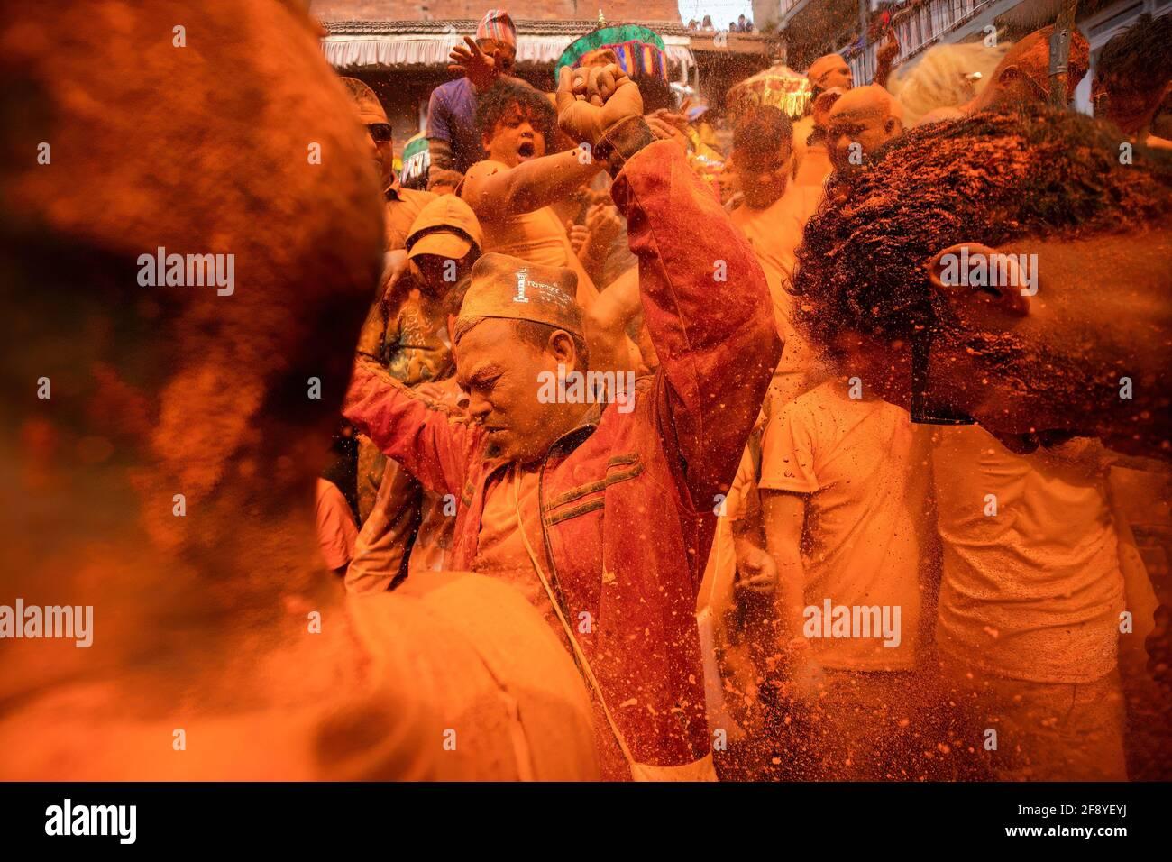 Bhaktapur, Nepal. 15 Aprile 2021. I popoli della comunità newari suonano strumenti tradizionali mentre gettano polvere di vermiglio (coperto) l'uno verso l'altro durante il festival indoor Jatra. I rivelatori portarono carri degli dei e delle dea indù e si gettarono vermilioni di polvere l'uno sull'altro come parte delle celebrazioni che iniziarono il nuovo anno nepalese. Credit: SOPA Images Limited/Alamy Live News Foto Stock