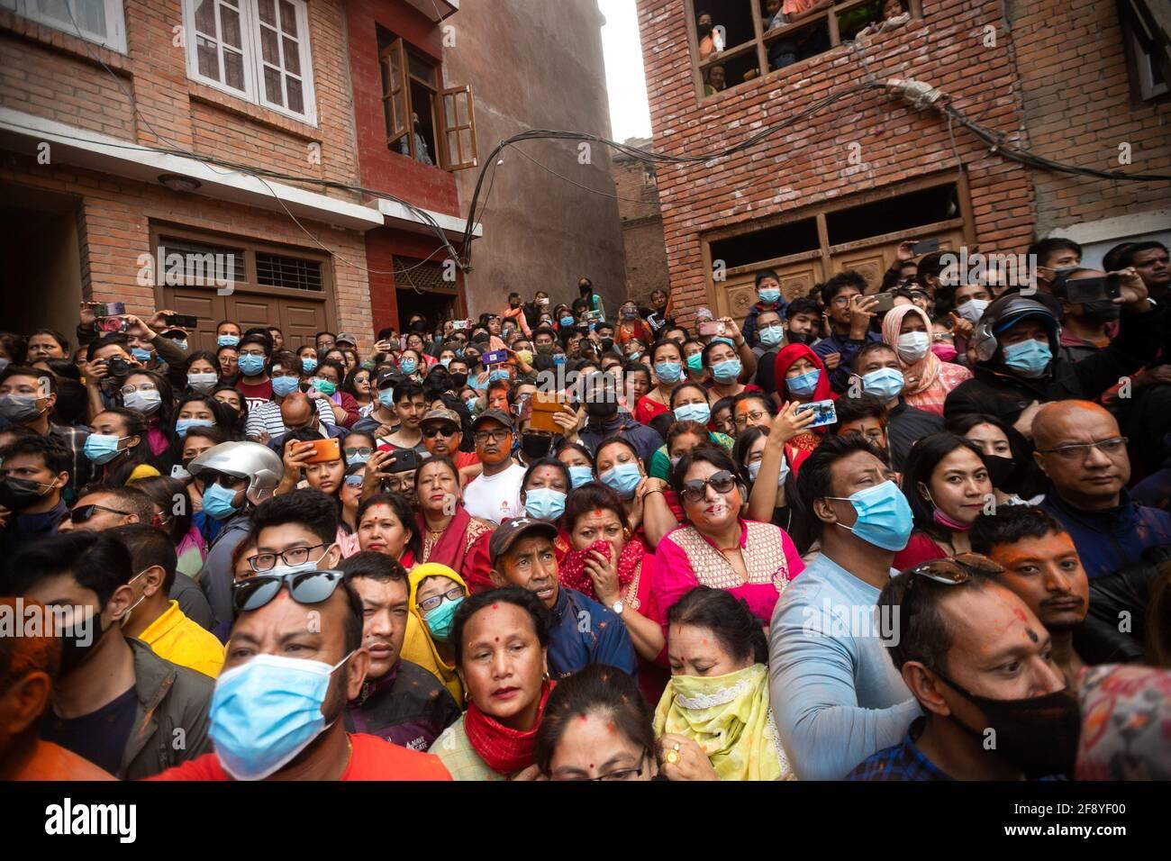 Bhaktapur, Nepal. 15 Aprile 2021. La gente osserva come i devoti celebrano il festival della polvere di vermillion di Jatra. I rivelatori portarono carri degli dei e delle dea indù e si gettarono vermilioni di polvere l'uno sull'altro come parte delle celebrazioni che iniziarono il nuovo anno nepalese. Credit: SOPA Images Limited/Alamy Live News Foto Stock