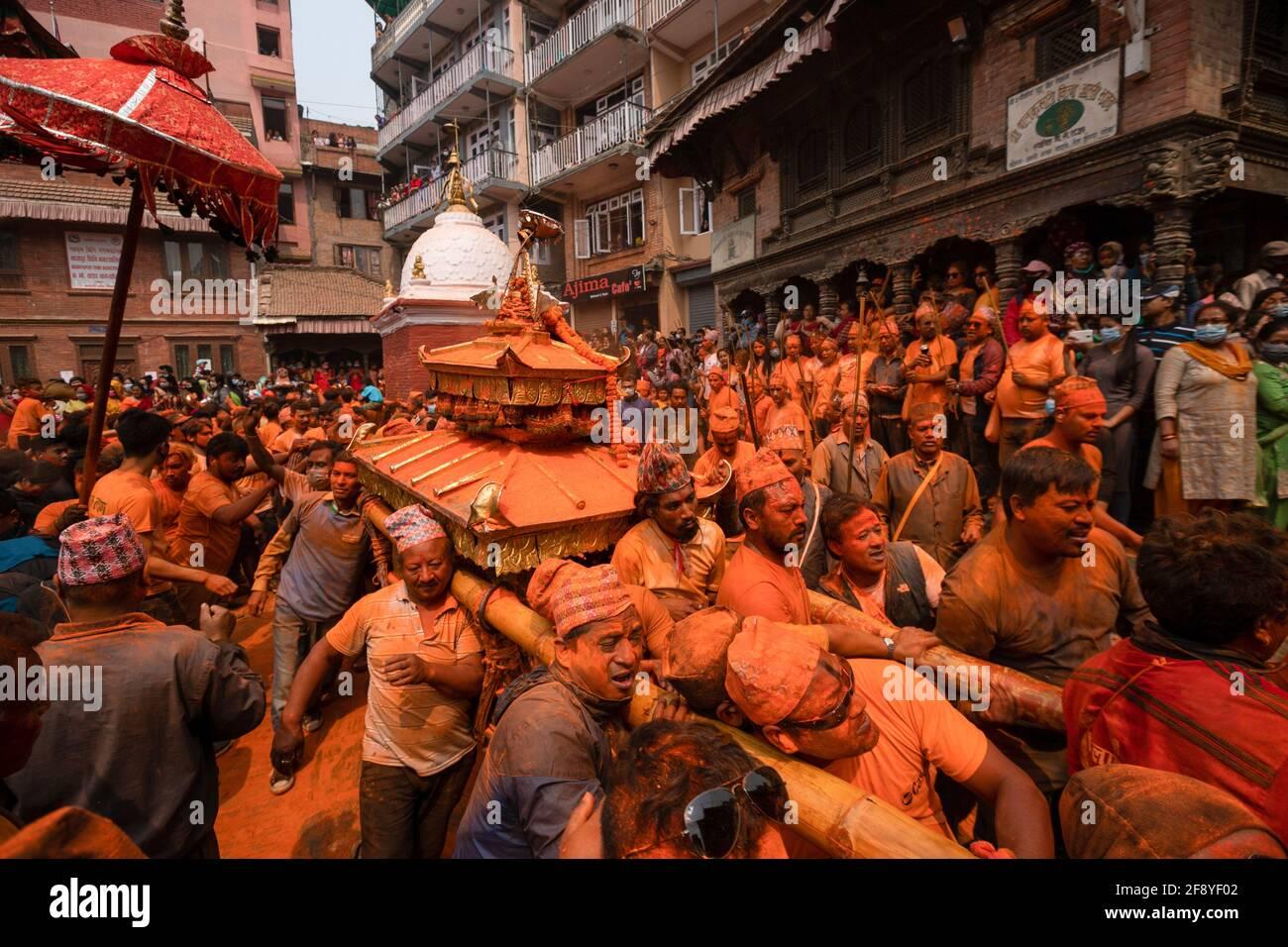 Bhaktapur, Nepal. 15 Aprile 2021. I devoti coperti di polvere di vermiglio portano un carro mentre girano il Tempio Balkumari durante il festival della polvere di vermillion di Jatra. I rivelatori portarono carri degli dei e delle dea indù e si gettarono vermilioni di polvere l'uno sull'altro come parte delle celebrazioni che iniziarono il nuovo anno nepalese. Credit: SOPA Images Limited/Alamy Live News Foto Stock