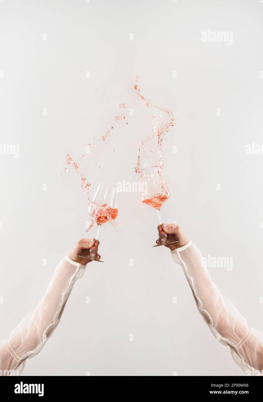 Mani femminili in eleganti camicie trasparenti bicchieri da versare con vino rosato fresco che vola in aria su fondo bianco. Degustazione di vini, vino s Foto Stock