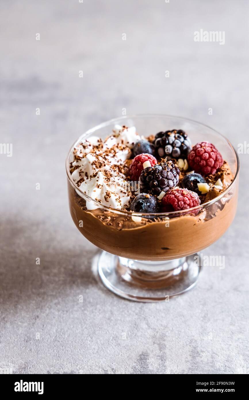Mousse al cioccolato con panna montata, frutti di bosco e cioccolato bianco Foto Stock