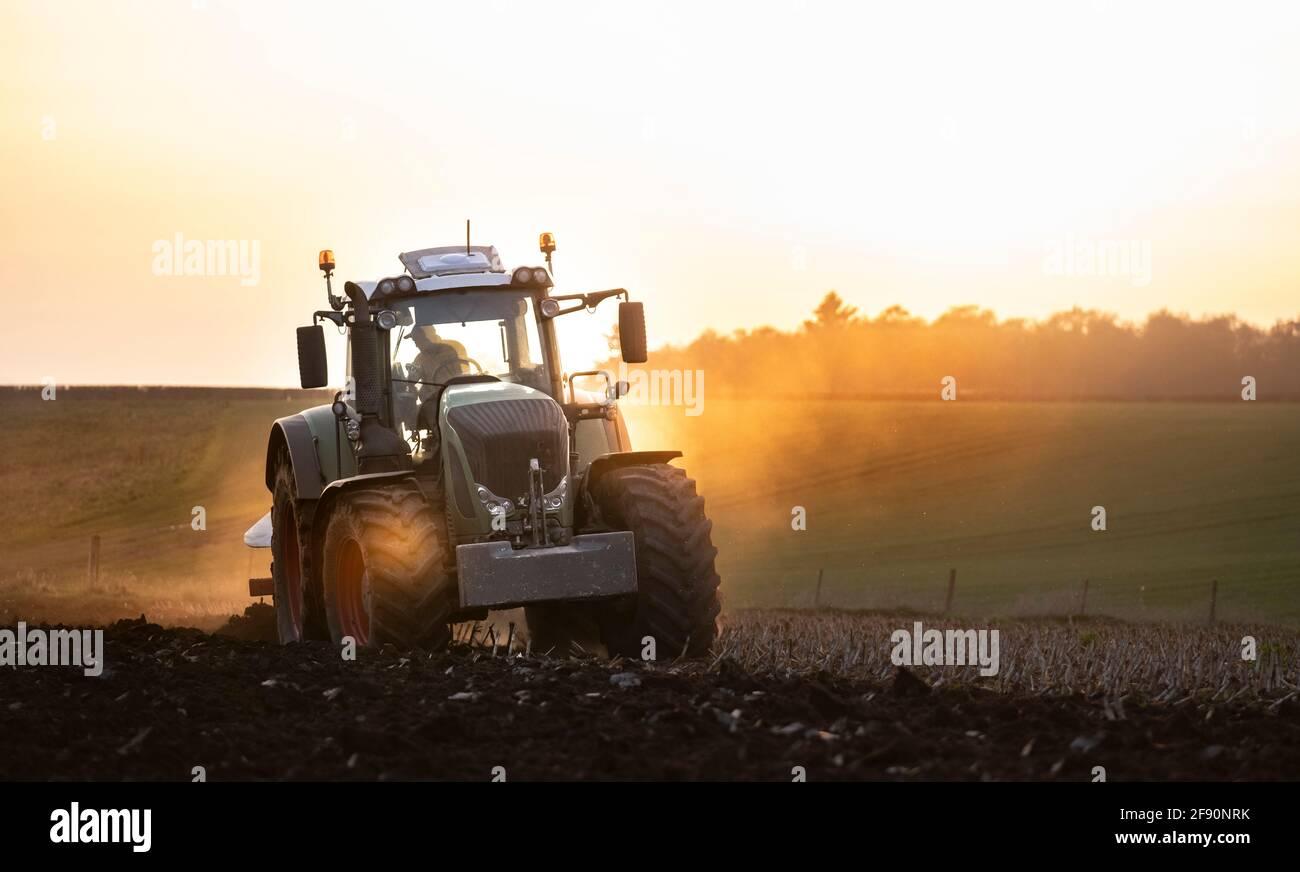 Aratura di un campo al tramonto con un trattore e un aratro, pronti per i raccolti in un'azienda agricola Foto Stock