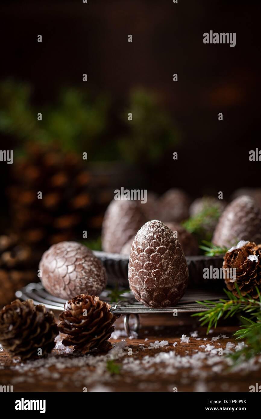 Cioccolatini festosi a forma di cono di pino su una rastrelliera metallica circondata da sprigs di abete e coni di pino reali Foto Stock