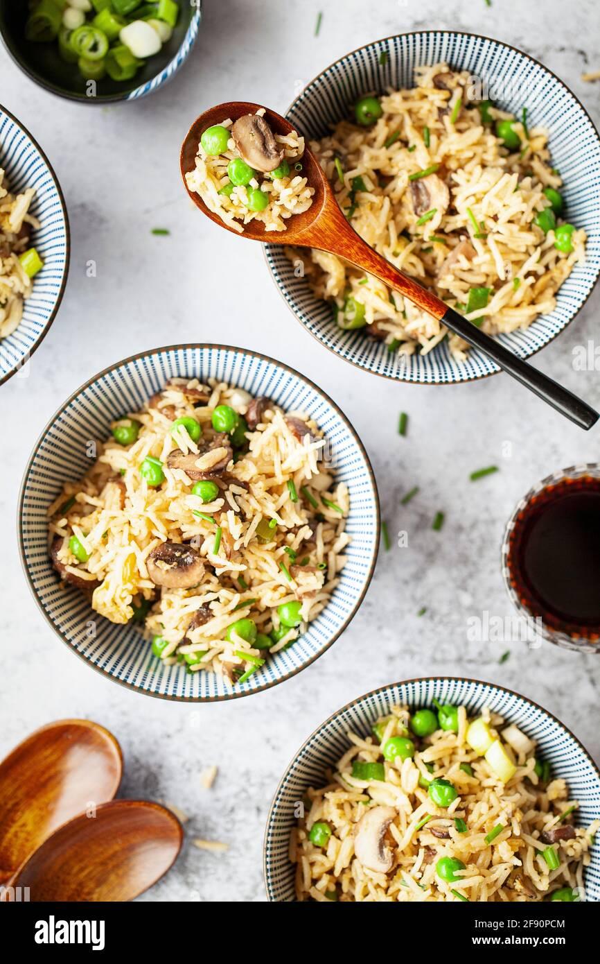 Riso fritto di funghi presentato in piccole ciotole con salsa di soia e cipolle di scalione servite insieme Foto Stock