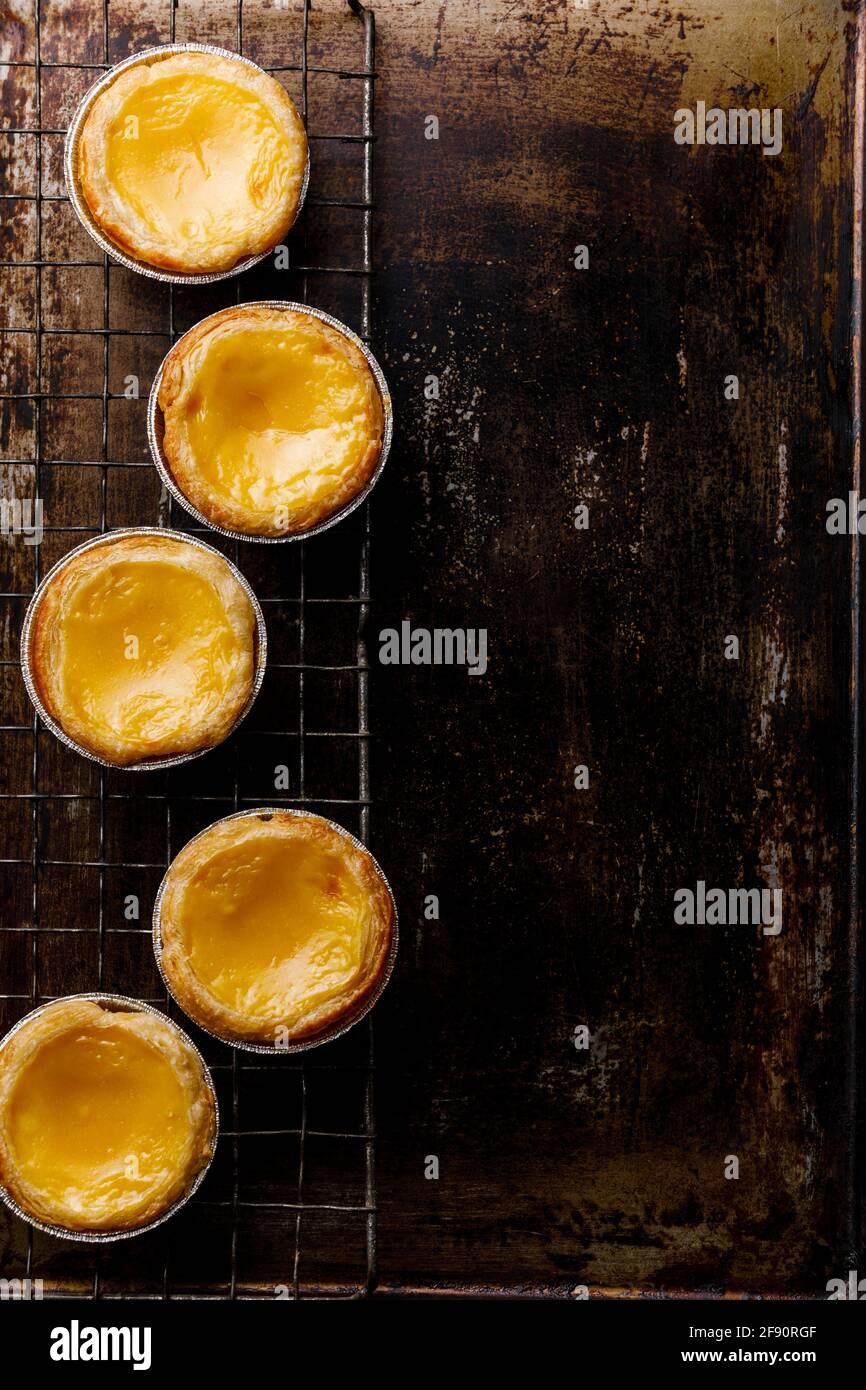 Pastel de Nata fresco cotto crema all'uovo portoghese Tart on spazio di copia del rack di raffreddamento Foto Stock