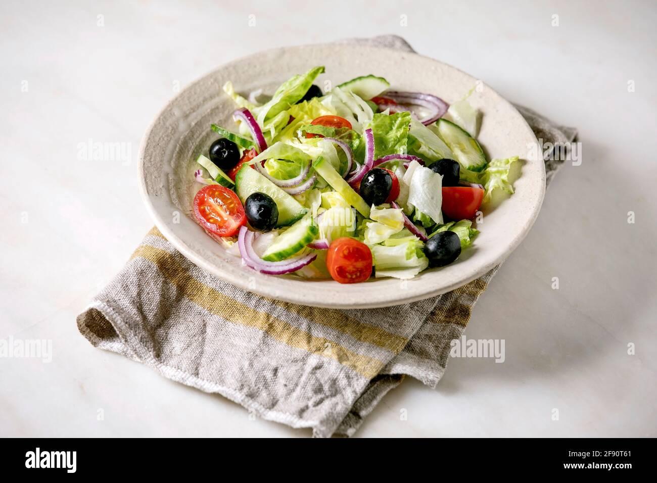 Insalata di verdure classiche con pomodori, cetrioli, cipolle, foglie di insalata e olive nere in piastra bianca in ceramica su tovagliolo di stoffa. Sfondo in marmo bianco. Foto Stock