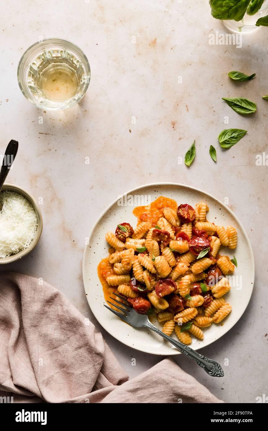 Piatto di cavatelli con pomodori ciliegini, piccola ciotola di parmigiano e bicchiere di vino. Foto Stock