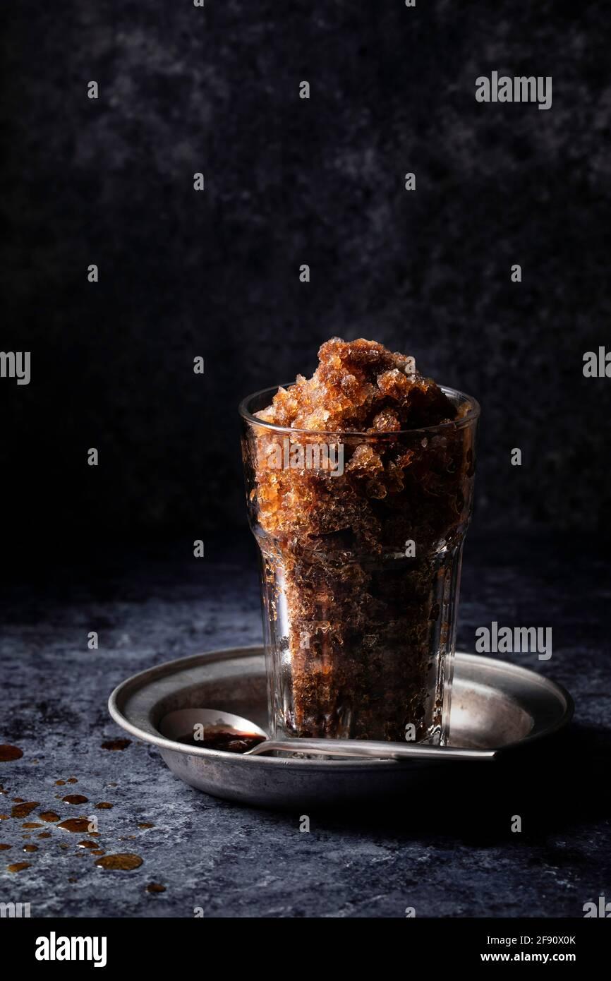 Caffè granita o ghiaccio rasato in un bicchiere su un superficie scura Foto Stock