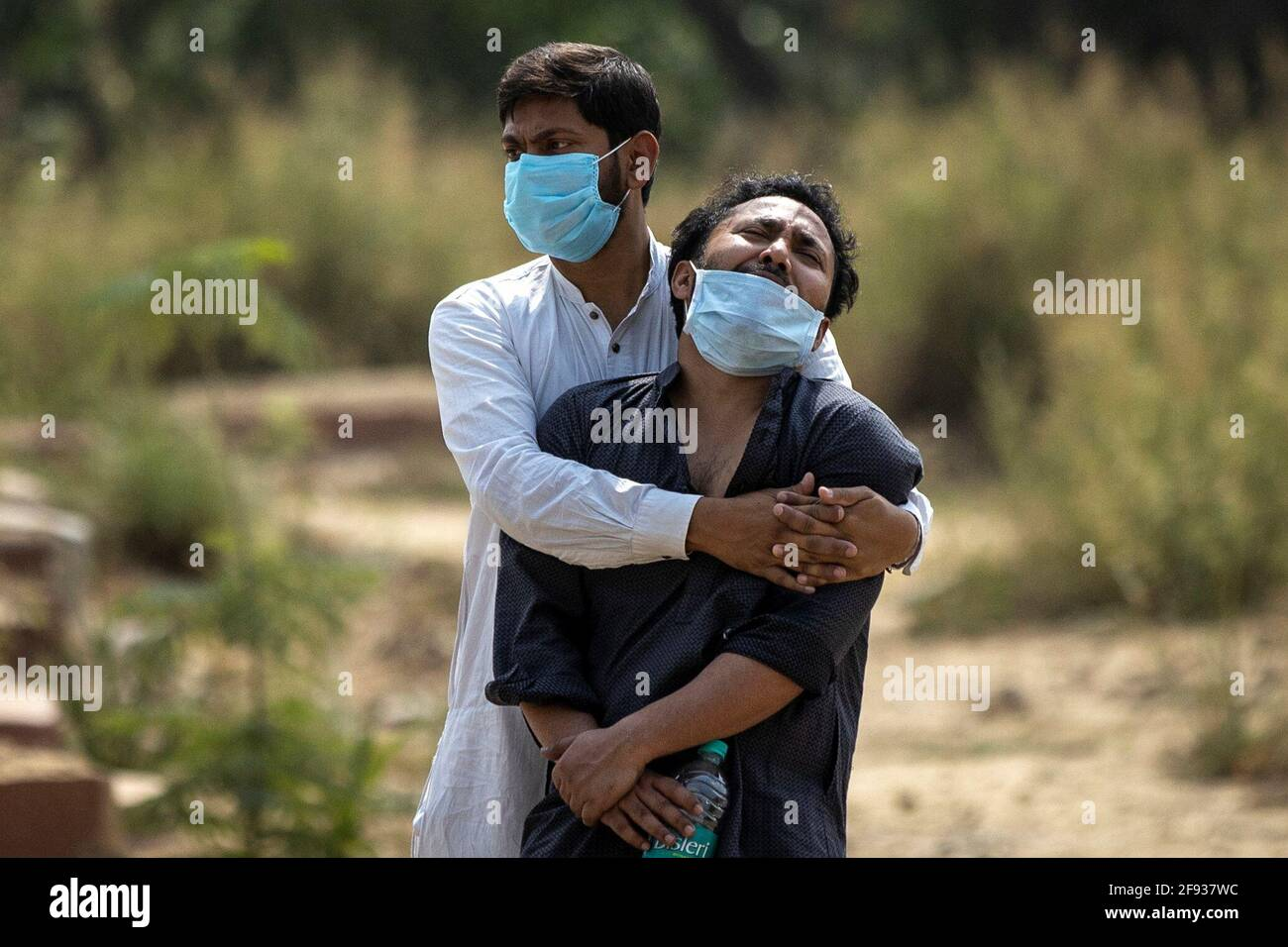 Un uomo è consolato dal suo parente come vede il corpo di suo padre, che è morto dalla malattia del coronavirus (COVID-19), prima della sua sepoltura in un cimitero a Nuova Delhi, India, 16 aprile 2021. REUTERS/Danese Siddiqui Foto Stock
