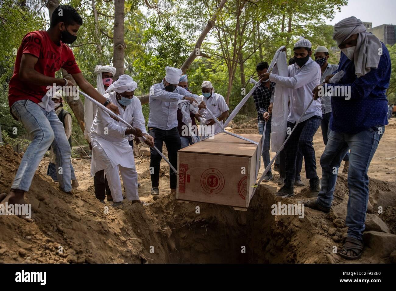 La gente seppellisce il corpo di un uomo, morto a causa della malattia del coronavirus (COVID-19), in un cimitero a Nuova Delhi, India, 16 aprile 2021. REUTERS/Danese Siddiqui Foto Stock