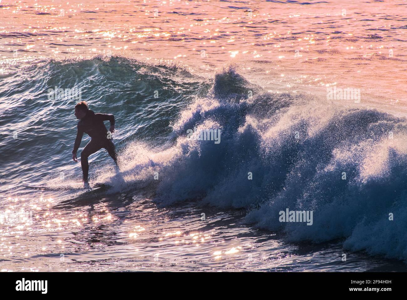 Un surfista a cavallo di un onda al Fistral a Newquay in Cornovaglia. Foto Stock
