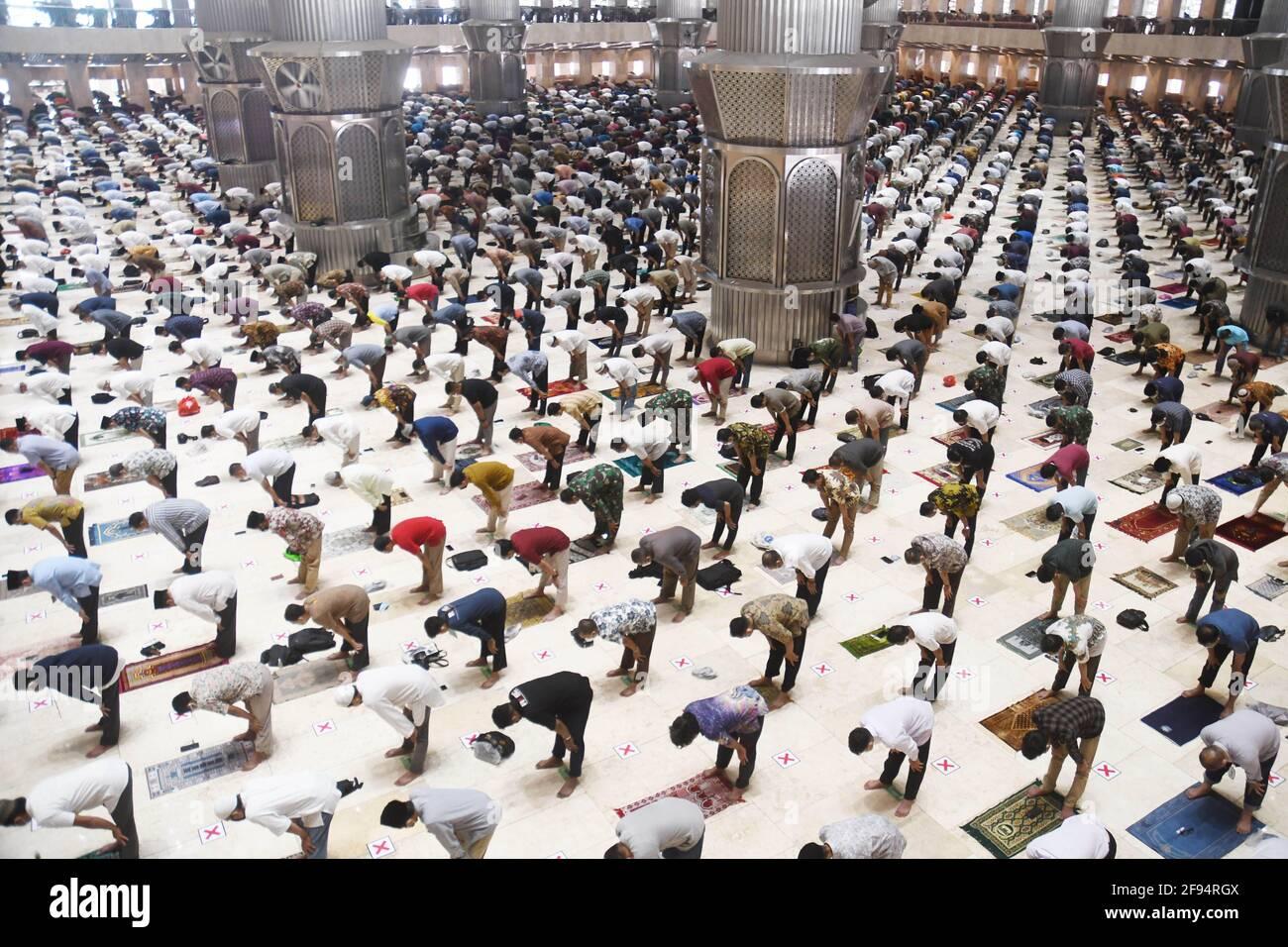 (210416) -- GIACARTA, 16 aprile 2021 (Xinhua) -- i musulmani partecipano alla preghiera del primo venerdì di mezzogiorno con distanza sociale durante il mese santo di Ramadan alla Moschea Istiqlal a Giacarta, Indonesia, il 16 aprile 2021. (Foto Dasril Roszandi/Xinhua) Foto Stock