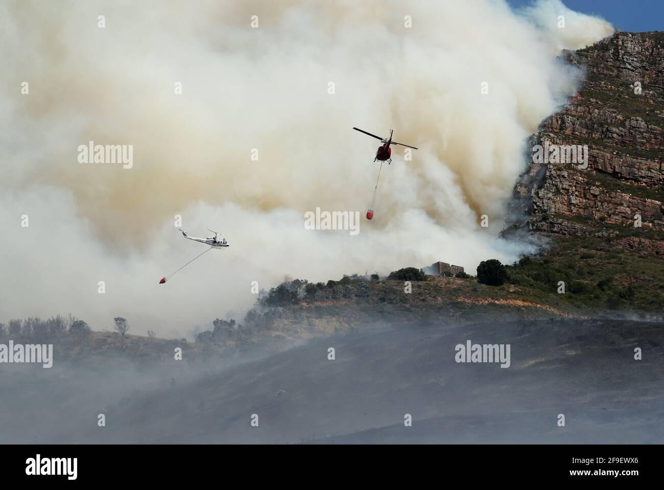 Gli elicotteri combattono per contenere un fuoco di funghi scoppiato sulle pendici di Table Mountain a Città del Capo, Sud Africa, il 18 aprile 2021. REUTERS/Mike Hutchings Foto Stock