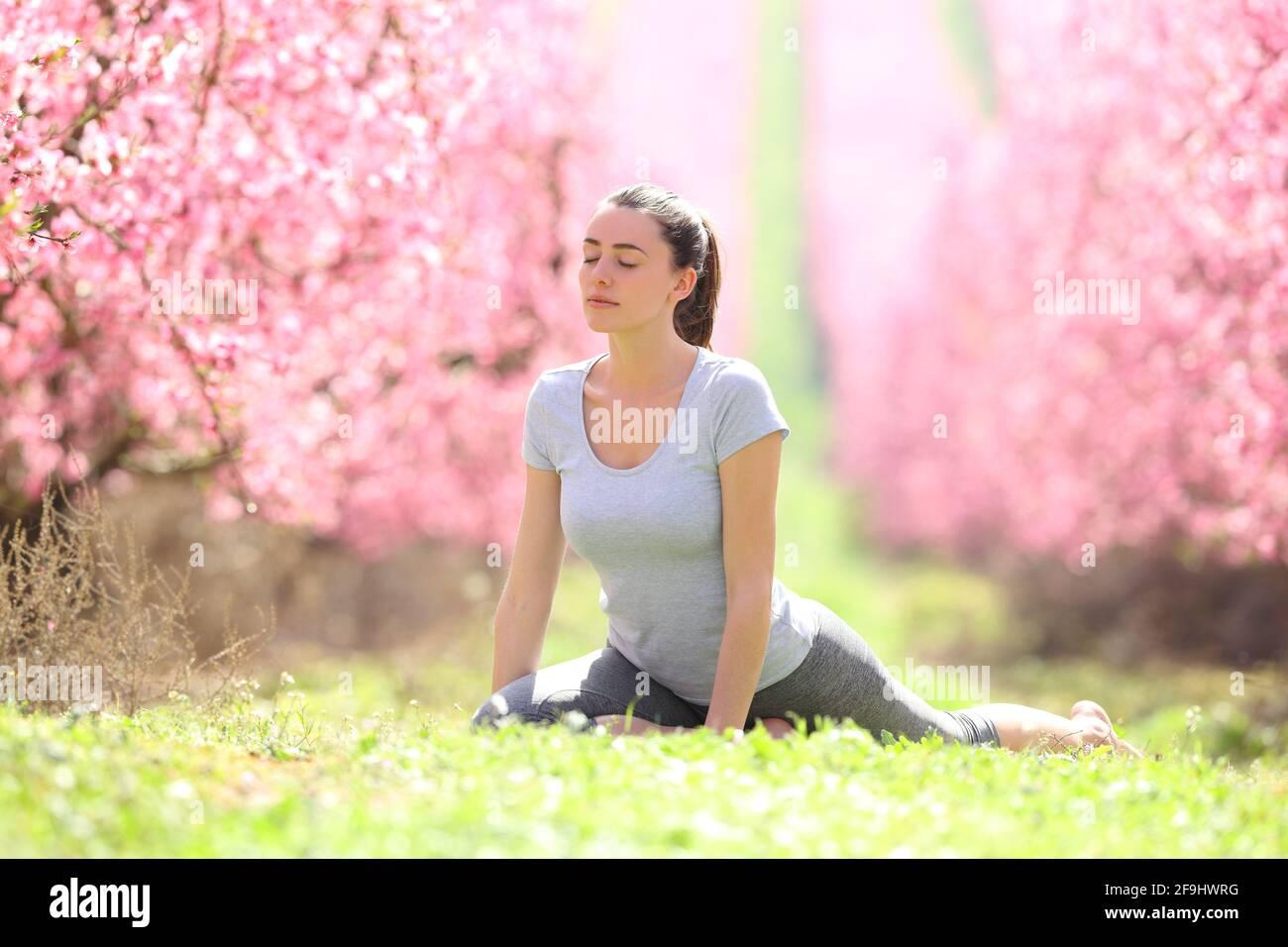 Donna concentrata che pratica l'esercizio di yoga sull'erba in un campo fiorito in primavera Foto Stock