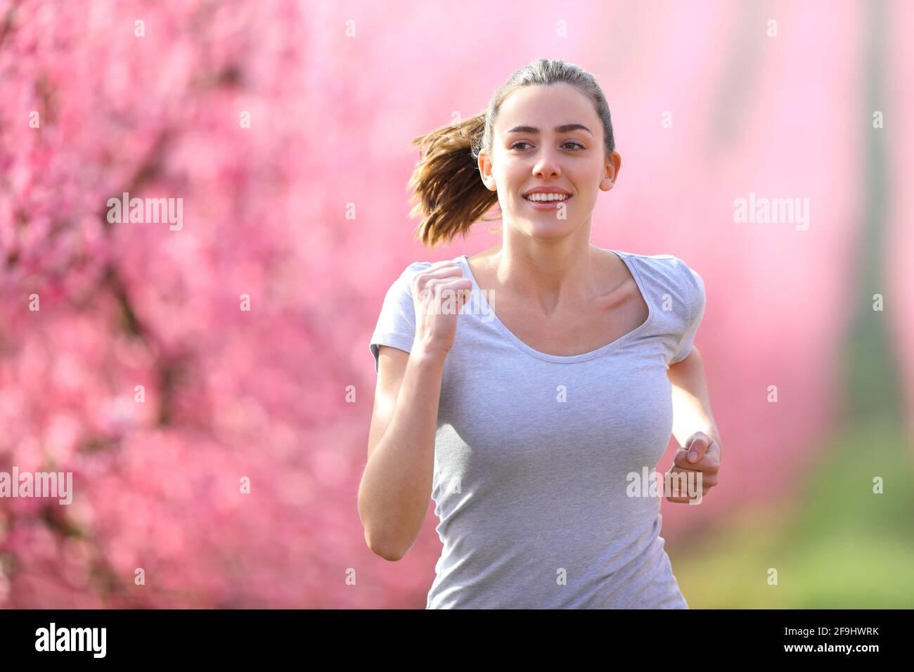Vista frontale ritratto di una donna felice che corre in un campo fiorito verso la telecamera Foto Stock
