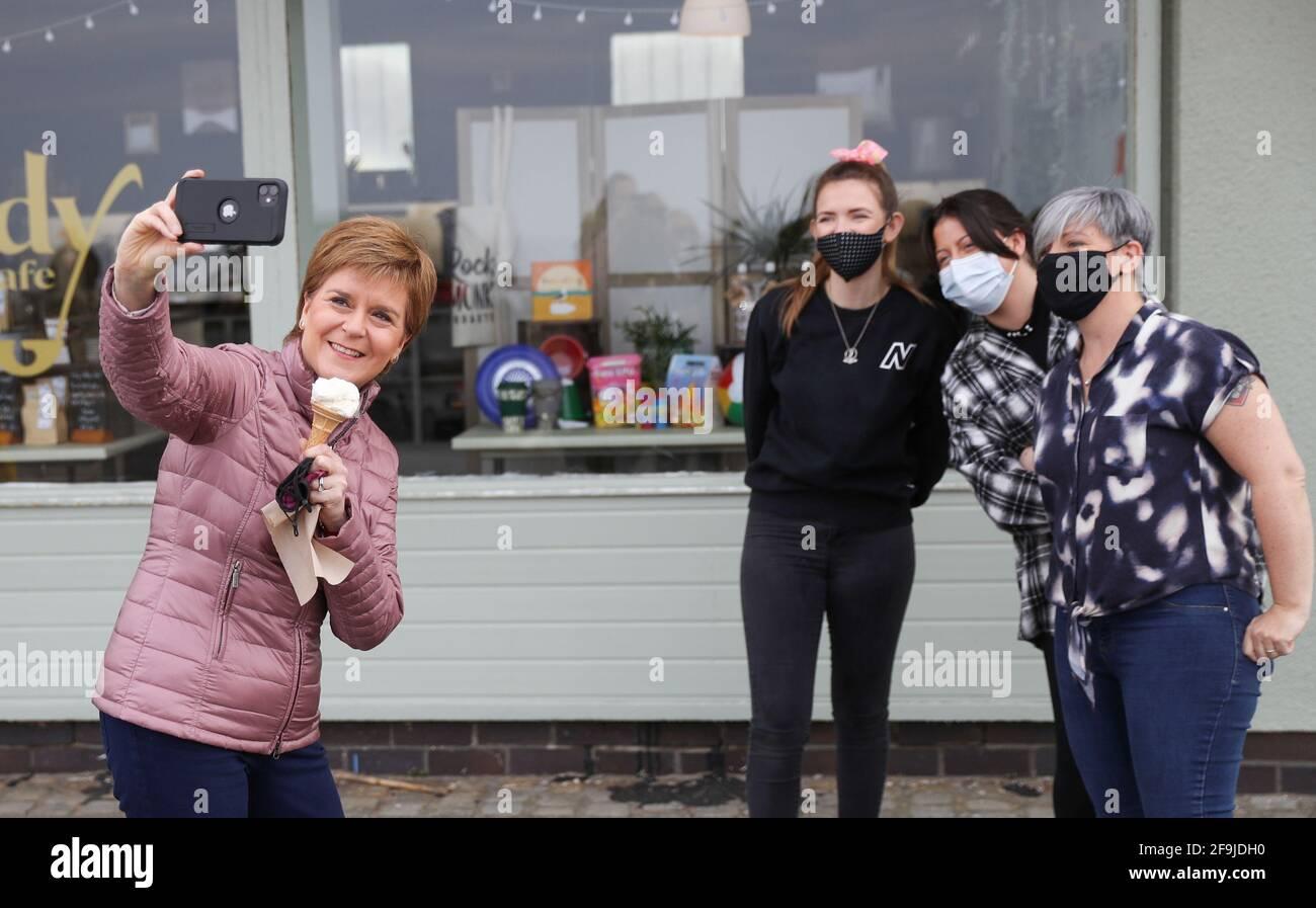 Il primo ministro scozzese Nicola Sturgeon, leader del Partito Nazionale Scozzese (SNP) (a sinistra), scatta una fotografia con tre donne ad Ayr, nell'Ayrshire meridionale, durante la campagna elettorale per le elezioni parlamentari scozzesi. Data immagine: Lunedì 19 aprile 2021. Foto Stock