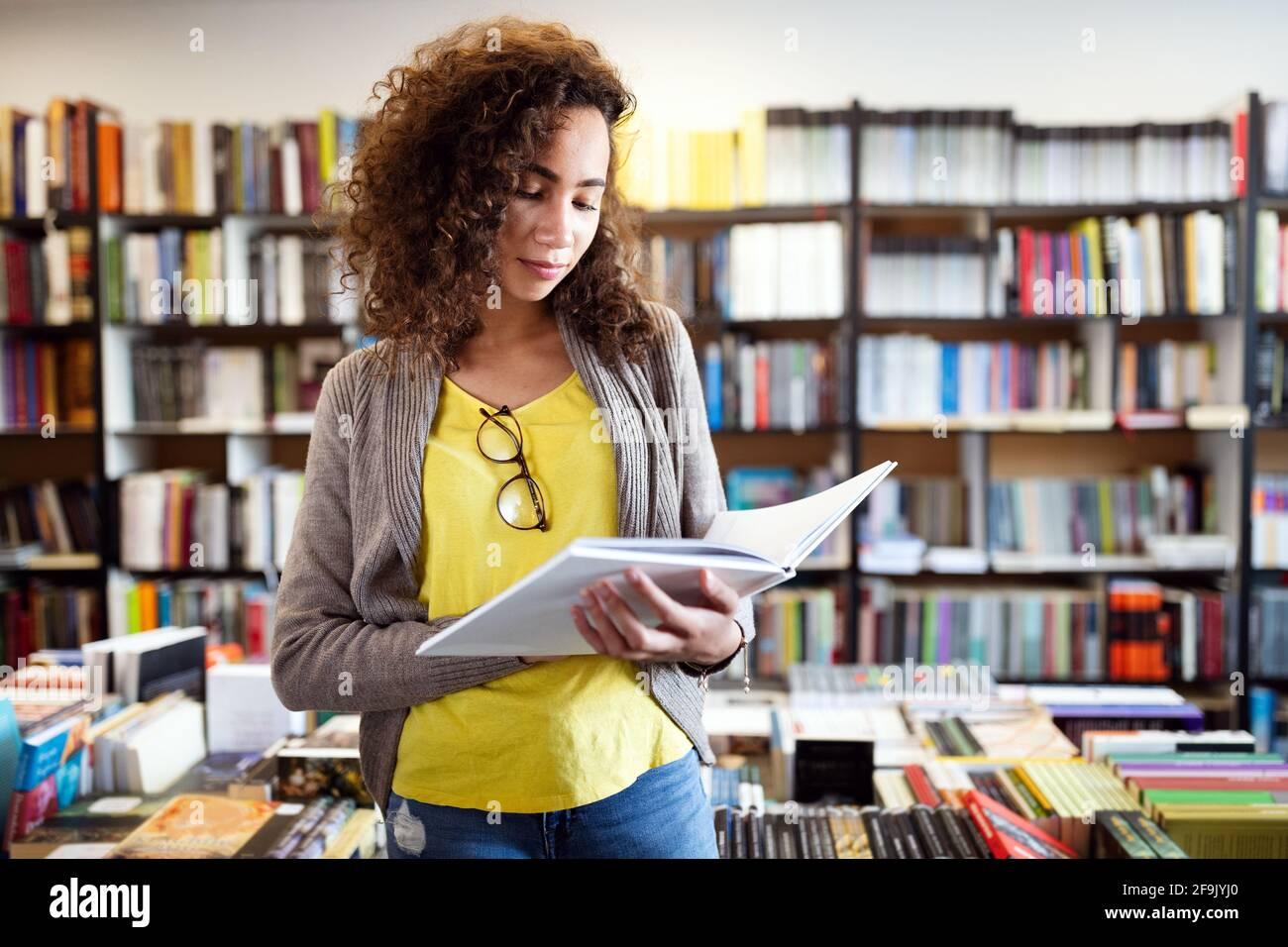 Istruzione, scuola superiore, università, apprendimento e concetto di persone. Libro di lettura sorridente della ragazza dello studente Foto Stock
