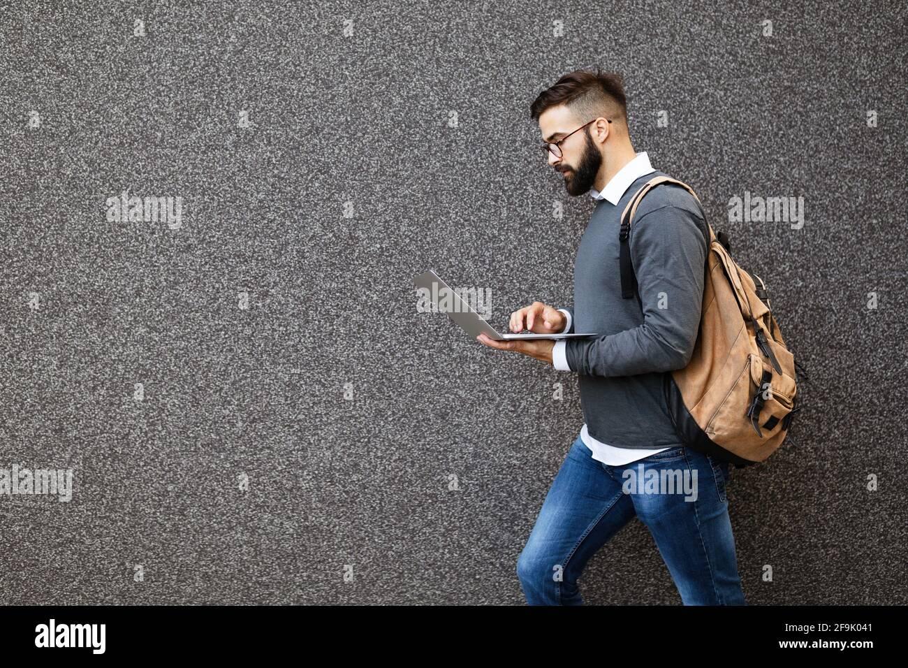 Uomo d'affari a piedi in strada tenendo il suo portatile, lavorando all'aperto Foto Stock