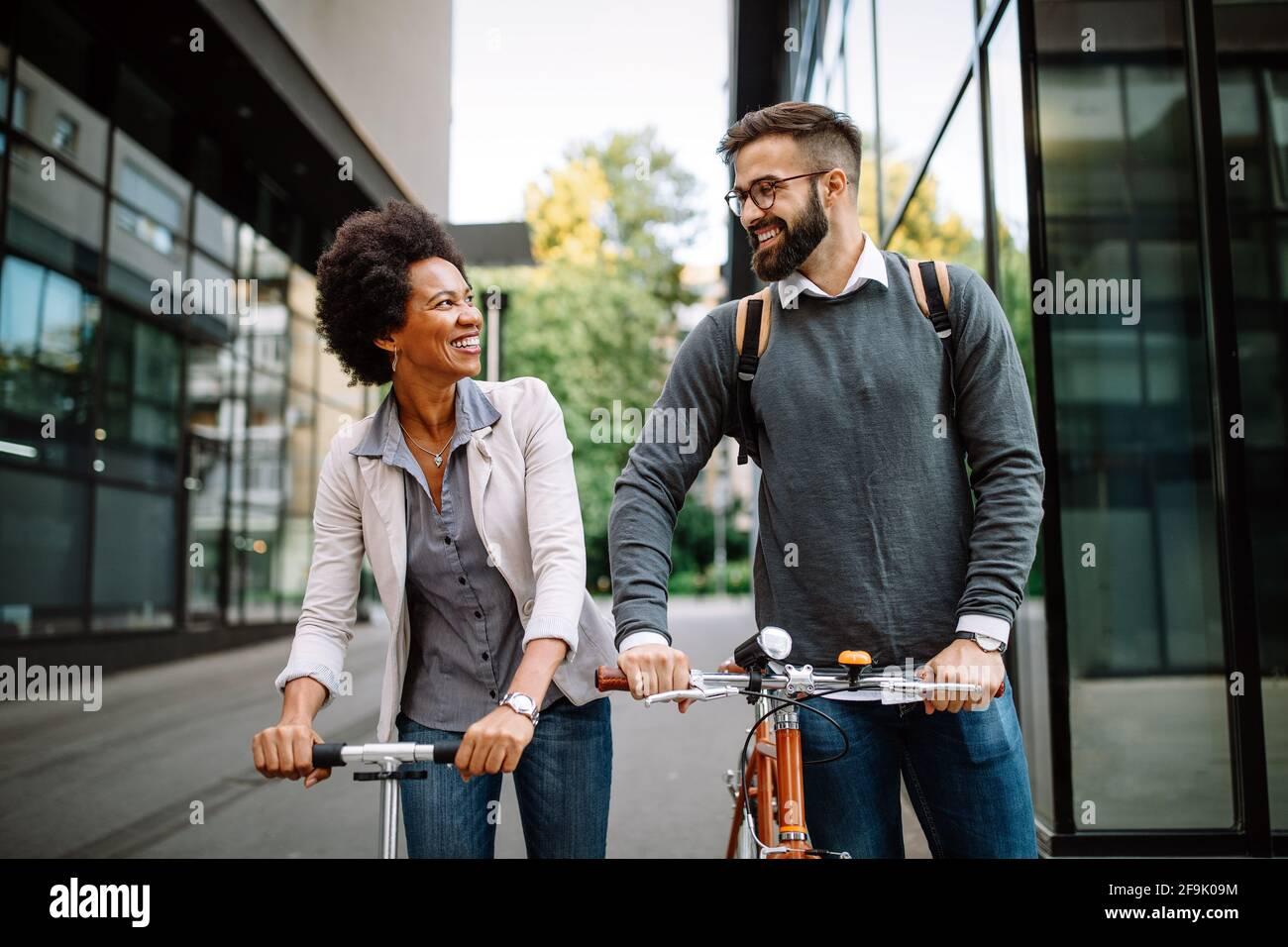 Gli uomini d'affari che lavorano con la bicicletta e lo scooter elettrico su strada urbana sono felici Foto Stock