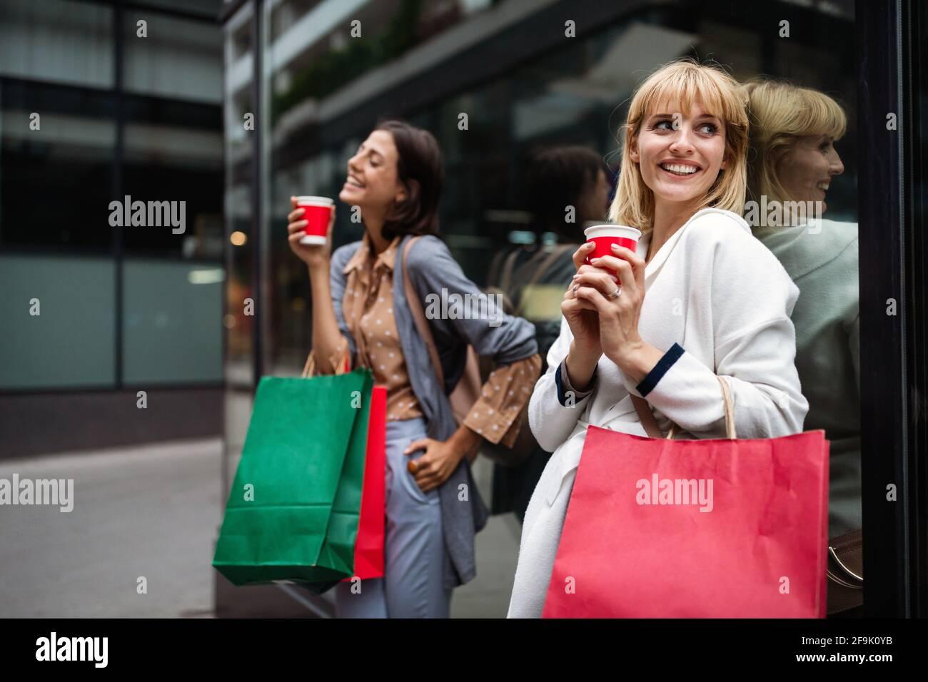 Giovani ragazze attraenti con le borse della spesa e caffè della città. Foto Stock