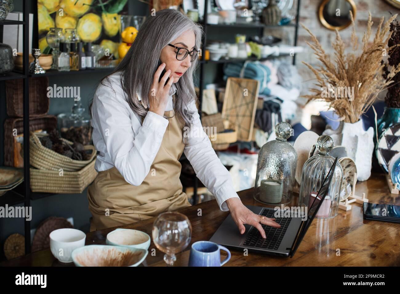 Venditore professionista con capelli grigi seduto al negozio di arredamento con un portatile aperto e parlare sul cellulare. Donna anziana che usa moderni gadget al lavoro. Foto Stock