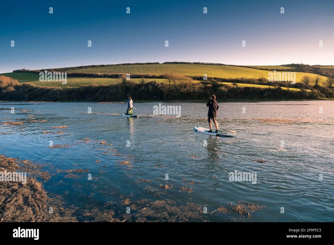Una famiglia di vacanzieri che si divertono a pagaiare le loro tavole Stand Up in alta marea sul fiume Gannel a Newquay in Cornovaglia. Foto Stock