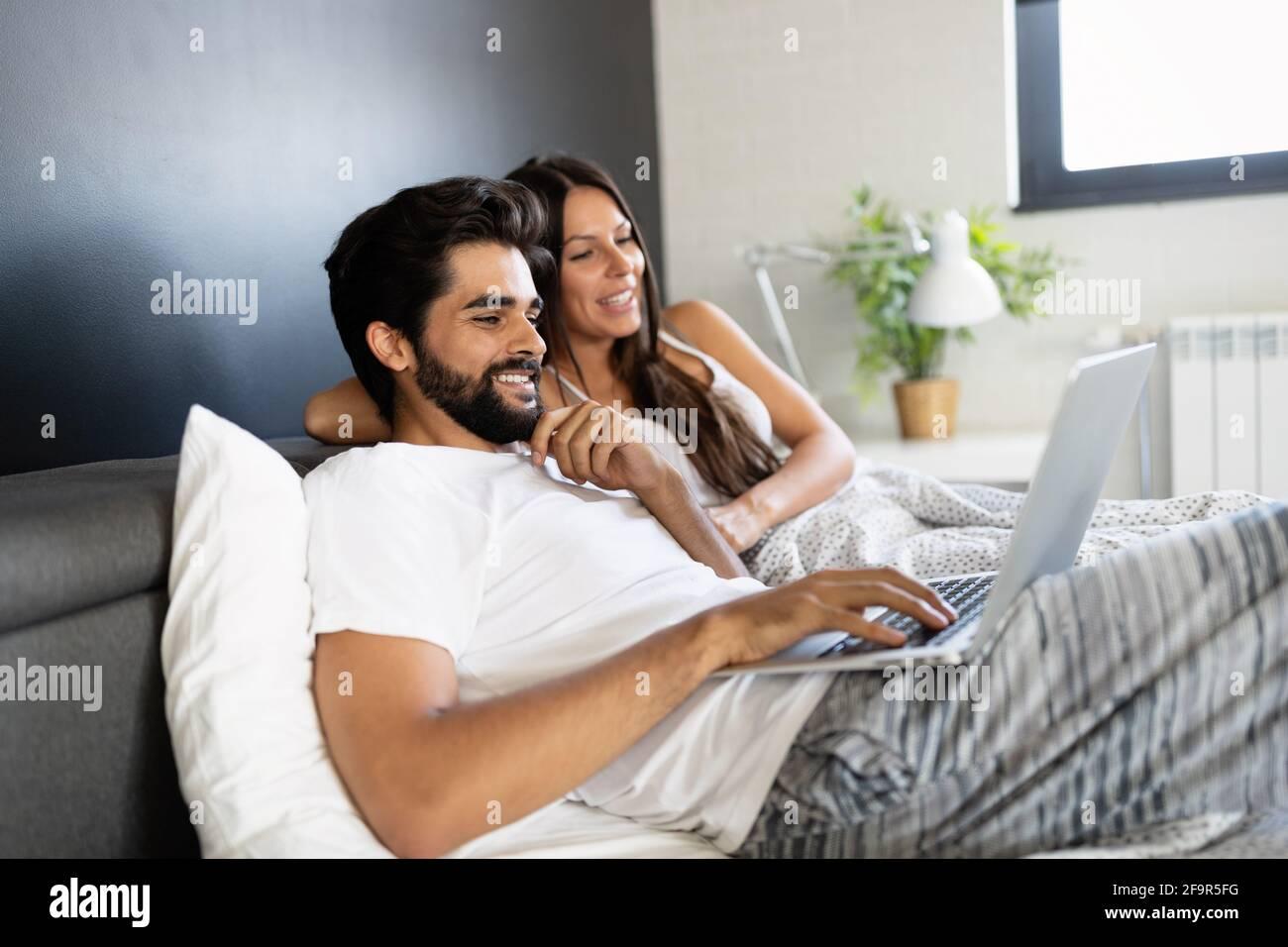 Giovane felice sorridente coppia con notebook in camera da letto Foto Stock