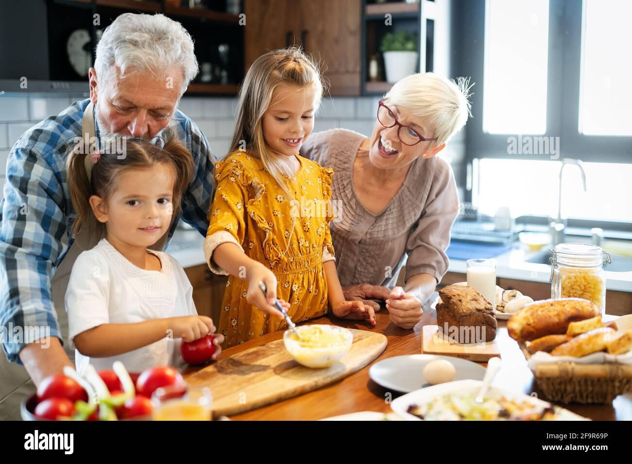 Felice grandchildrens ragazze avente la colazione con i suoi nonni Foto Stock