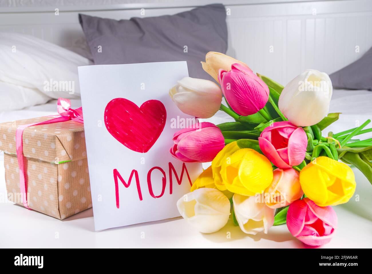 Giorno della mamma, giorno della figlia concetto di stile di vita di vacanza. Bambino preschooler bambina bionda ragazza con un bouquet di fiori di tulipano, biglietto d'auguri fatto a mano Foto Stock