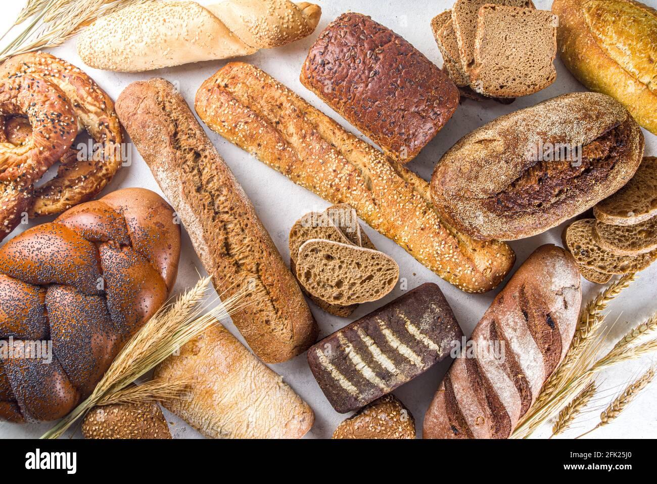 Assortimento di vari deliziosi pane appena sfornato, su sfondo bianco, area copia vista dall'alto Foto Stock