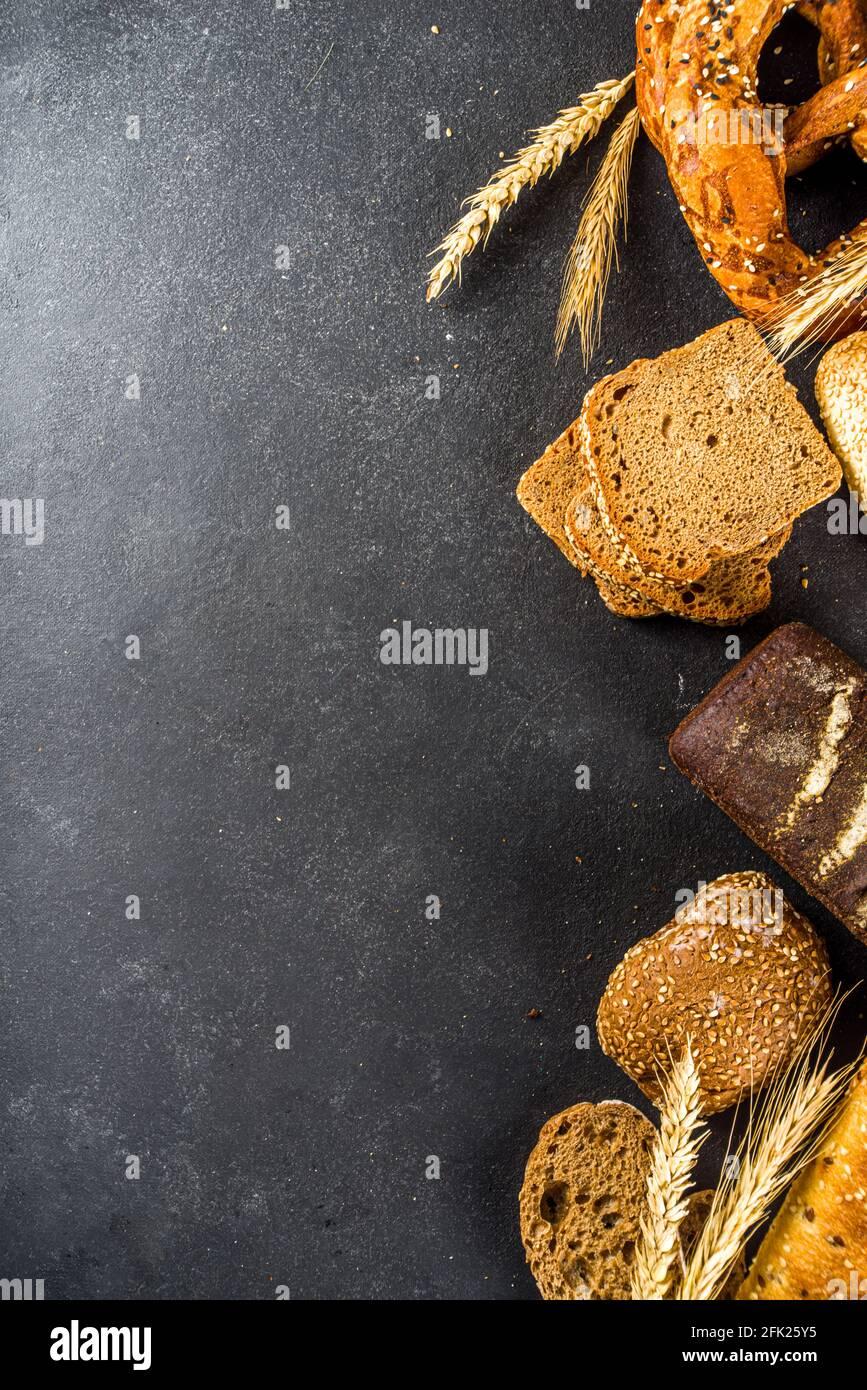 Assortimento di vari deliziosi pane appena sfornato, su fondo nero cemento vista dall'alto spazio copia Foto Stock