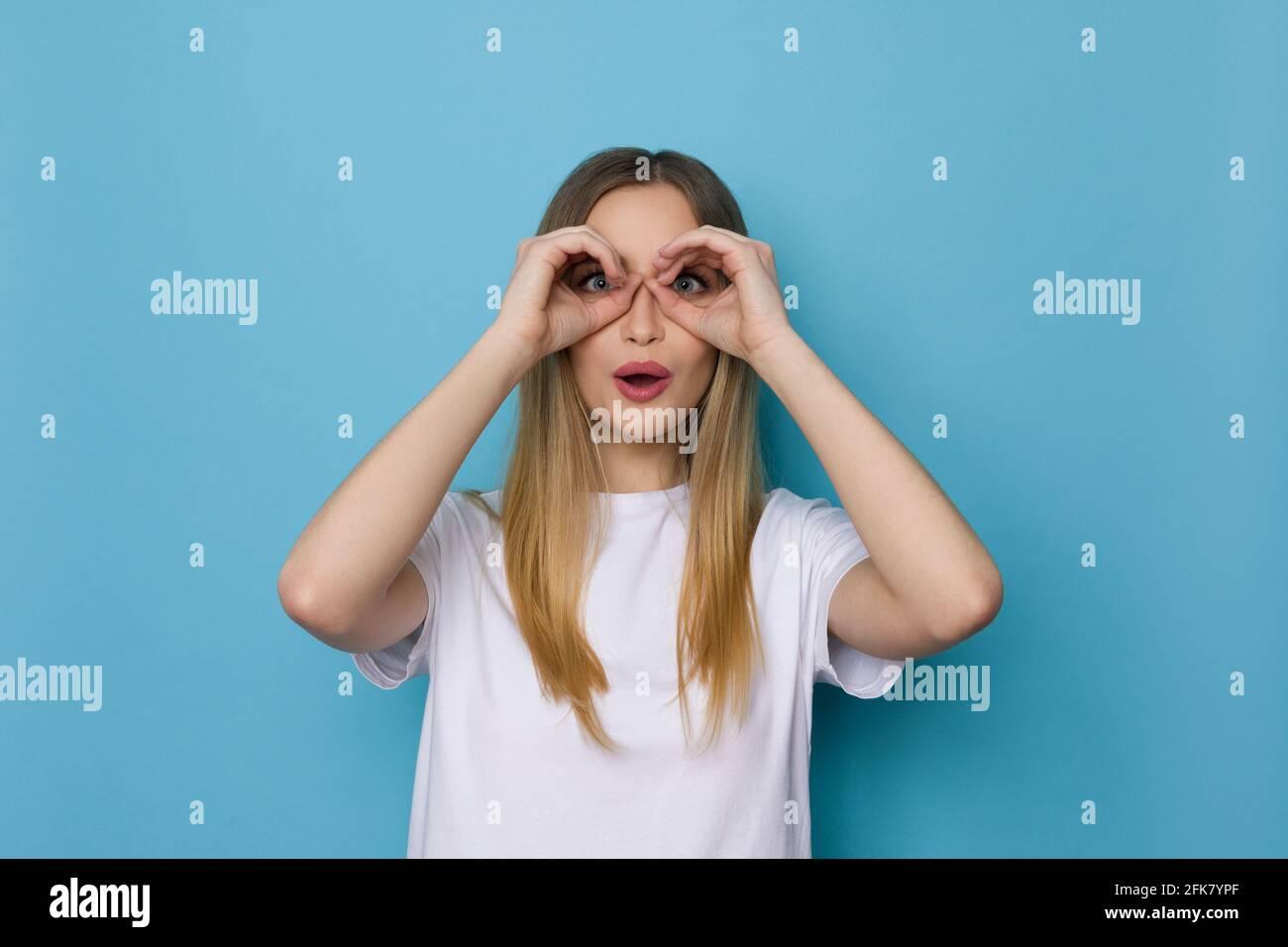 Sorpresa giovane donna in camicia bianca sta facendo mani binocolo e guardando la macchina fotografica. Girata in casa su sfondo blu. Foto Stock