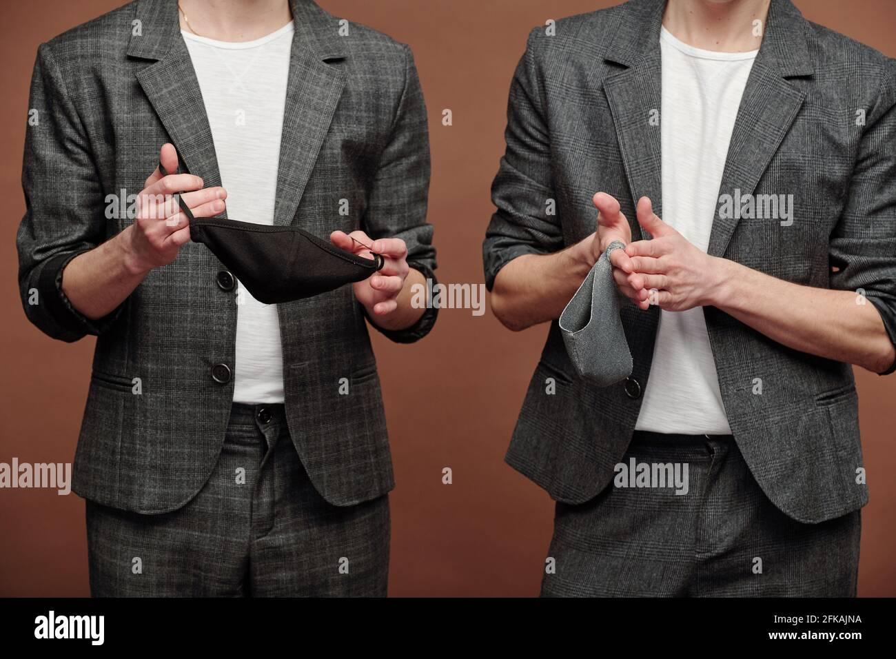 Primo piano di uomini irriconoscibili in abiti casual eleganti che tengono un panno maschere su sfondo marrone Foto Stock
