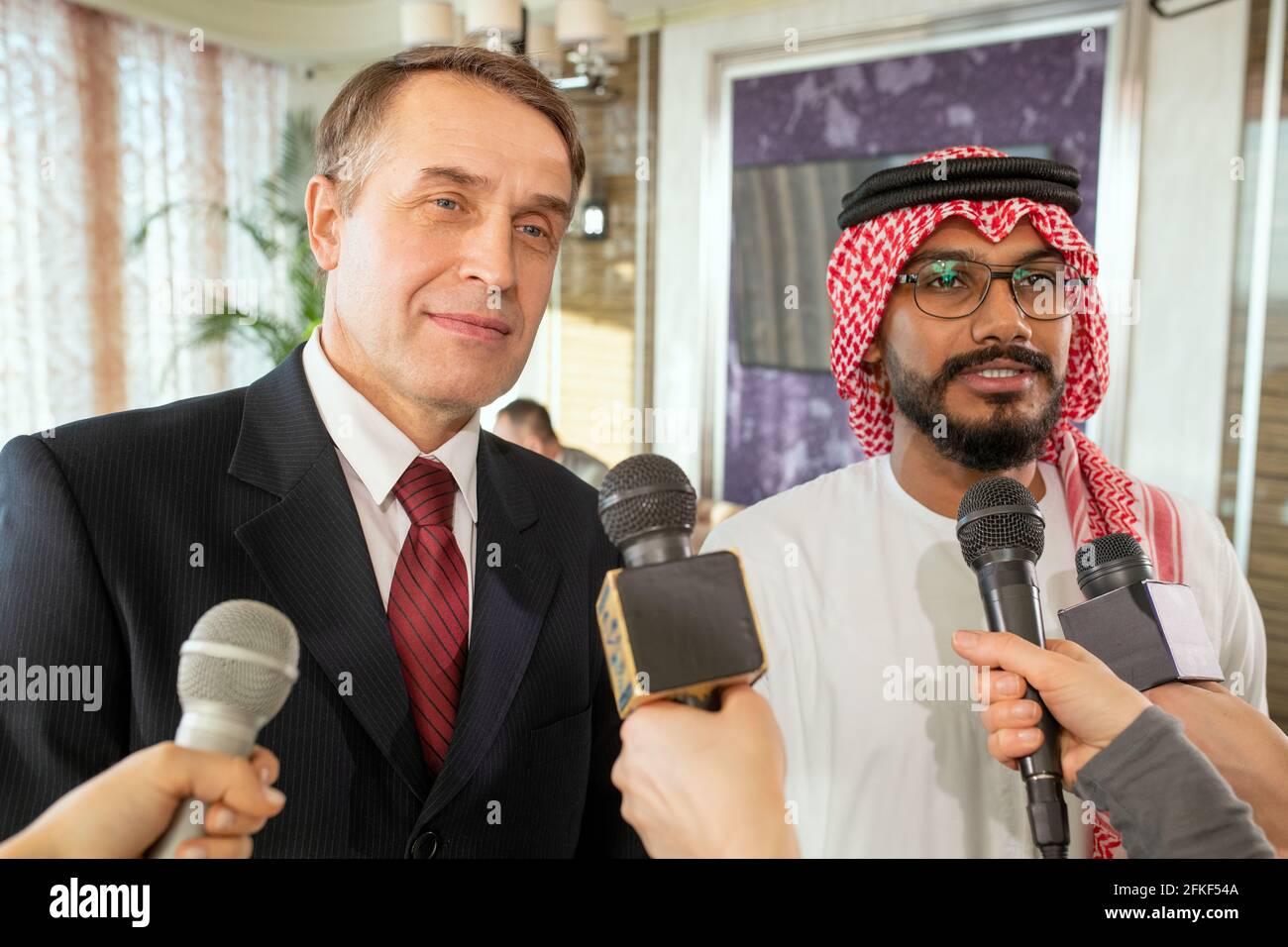 Uomini d'affari in piedi davanti ai giornalisti con microfoni durante l'intervista Foto Stock
